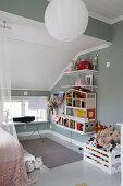 Puppenhaus, Regale und Kiste mit Spielzeug im Mädchenzimmer mit grauer Wand und Dachschräge