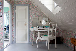 Typewriter on vintage desk and chair in attic room with floral wallpaper
