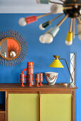 Collection of ceramics and table lamp on retro sideboard below sunburst mirror on blue wall