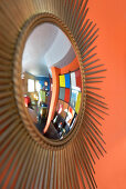 Sunburst mirror on orange wall