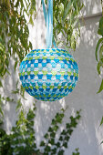 Lantern with blue and green crocheted cover