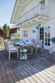 Sommerlich gedeckter Tisch vor einem weißen Landhaus