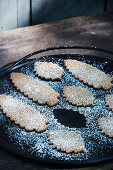 Leaf-shaped biscuits dusted with icing sugar on tray
