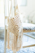 Macrame bag hung from chair backrest