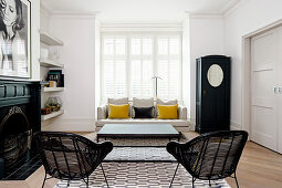 Black-and-white living room with two yellow scatter cushions on sofa