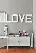 Lettering spelling 'LOVE' on grey wall above white metal sideboard