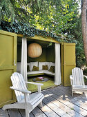 Two deckchairs on terrace outside climber-covered summerhouse