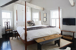 Four-poster bed and old benches in bedroom with exposed roof structure