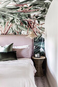 Bed with headboard on wallpapered wall with plant motif in bedroom