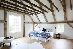 Exposed roof structure and beams in large bedroom
