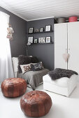Two leather pouffes, easy chair and ottoman in front of cupboard against grey wall