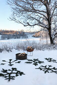 Decoratively arranged pine branches and fire bowl in snowy landscape