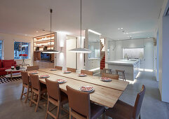 Leather chairs in elegant dining area in front of kitchen and lounge areas