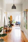 Zimmerpflanzen in breitem Flur mit Holzdielenboden, Blick ins Wohnzimmer