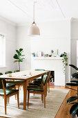Tisch mit Stühlen vor Kamin und Zimmerpflanze in weißem Esszimmer