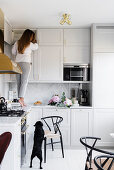 Woman standing on counter in pale grey fitted kitchen with marble splashback