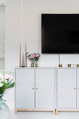 Candles on pale grey base units below TV mounted on wall