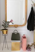 Gilt-framed mirror, plant stand, handbag and brass coat stand in white hallway