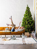Blond woman lying on ocher sofa in front of Christmas tree