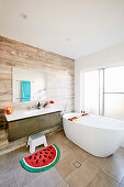 Freestanding bathtub in front of sliding glass door, vanity and bath mat with melon motif in the bathroom