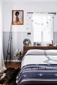 Double bed in front of the window, framed photo and fishing rod in the bedroom, folding chair with wrapped presents