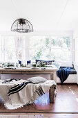 Christmas dining table, matching bench with blanket and pillow and built-in bench in front of the window