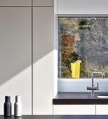 Patterns of straight lines and sunshine in minimalist modern kitchen