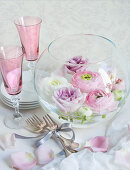 Wedding decorations: flowers in glass bowl, Champagne flutes and cutler on table