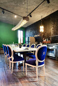 Antique chairs with velvet upholstery around long dining table in front of kitchen counter in renovated loft apartment