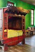 Antique Chinese wedding bed against green wall in renovated loft apartment