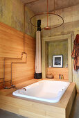 Bathtub and shower with copper fittings in wood-panelled bathroom