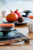 Table set in Oriental style with Hokkaido pumpkins on plate