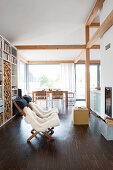 Fur blankets on loungers in front of fireplace in open-plan interior