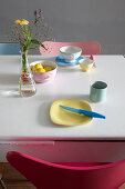 Colourful breakfast crockery on white table
