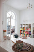 Side table and classic rocking chair on crocheted rug in front of bookcase