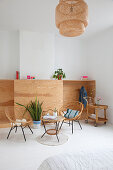 Vintage rattan chairs, table and serving trolley in front of half-height wardrobe with open front
