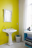 Pedestal sink and mirror on yellow wall in bathroom