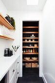 Narrow white room with view into pantry