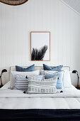 Doppelbett mit blauer Tagesdecke im Schlafzimmer mit weißer Holzverkleidung