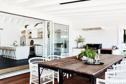 Esstisch mit rustikaler Holzplatte und weißen Rattanstühlen