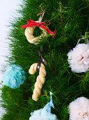 Bunte Pompons und Gebäckkringel an Weihnachtsbaum