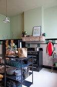Blick in die Küche mit offenem Geschirrregal und mintgrüner Wand