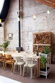 Gedeckter Tisch mit Stühlen und Holzlager vor Backsteinwand