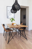 Dining table and various chairs below black pendant lamps