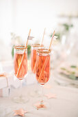 Three gold-rimmed glasses of pink sparkling wine with straws
