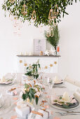 Modern place settings on white Christmas table below bunch of mistletoe