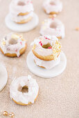 Donuts with pink icing decorated with pink sprinkles and gold leaf