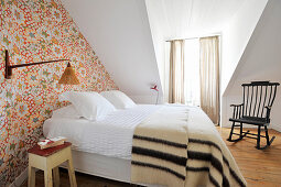Double bed and patterned wallpaper in attic guest room