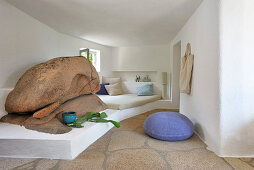 Bed on masonry platform next to boulders