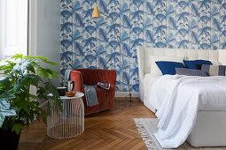 Blue-and-white, leaf-patterned wallpaper and designer furniture in bedroom